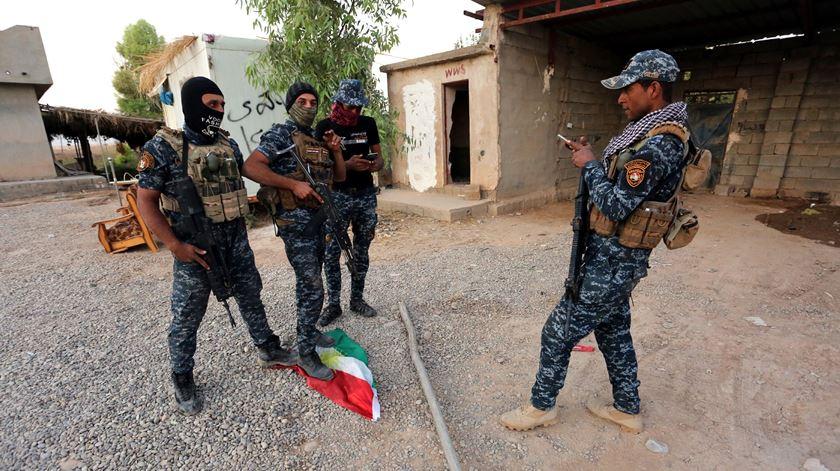 Militares iraquianos pisam uma bandeira curda em Kirkuk. Foto: Murtaja Lateef/EPA