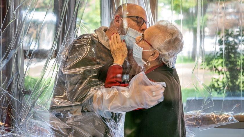 Filho cumprimenta mãe num lar de idosos, através de um separador de plástico. Foto: Facebook / Centro Servizi Persona Domenico Sartor