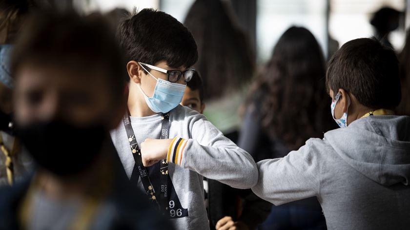 Duas crianças inovam no momento de se cumprimentarem, na tentativa de manterem o distanciamento necessário devido à pandemia de Covid-19, no regresso às aulas. Foto: Joana Bourgard/RR
