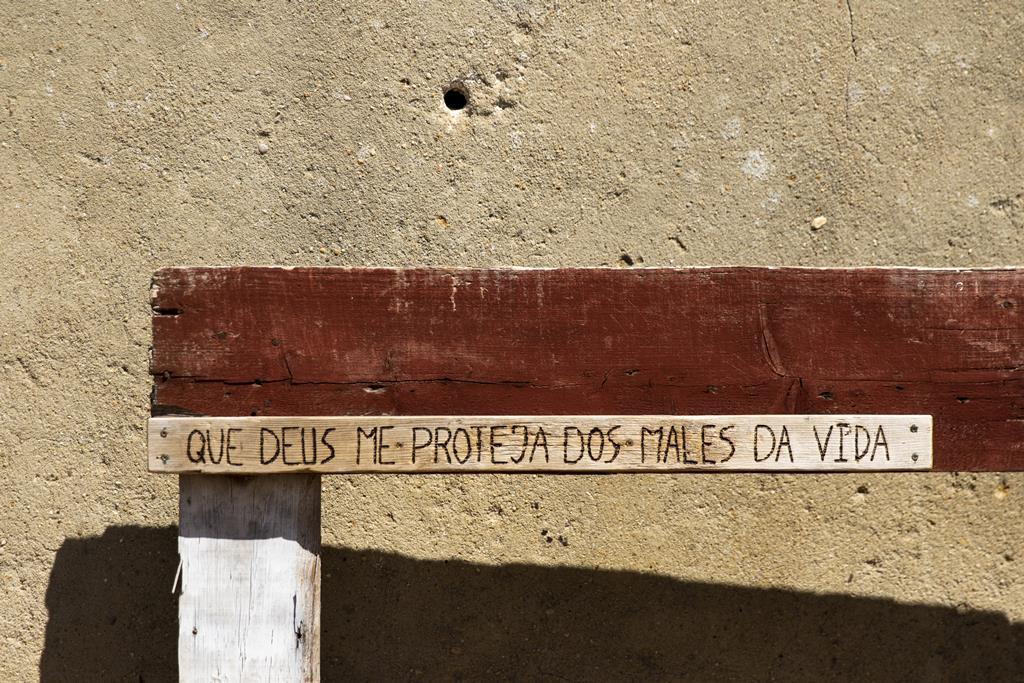 Inscrição num banco de madeira, à entrada do bairro.