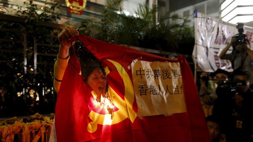 Manifestante queima bandeira da China em Hong Kong. Foto: Tyrone Siu/Reuters