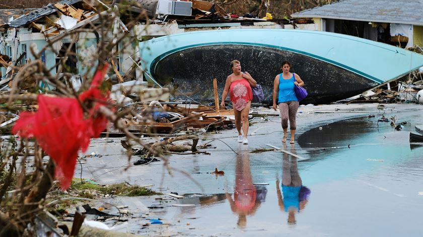 Mulheres caminham entre os estragos em Marsh Harbour. Foto: REUTERS / Dante Carrer