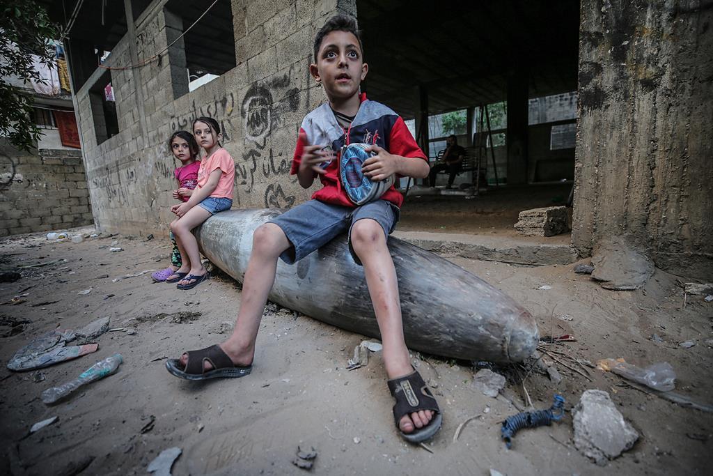 Crianças palestinianas sentadas num míssil por explodir disparado por aviões de guerra israelitas, após ataques aéreos , na cidade de Gaza. Foto: Mohammed Saber/EPA