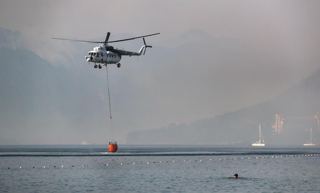 Helicóptero carrega água para combater incêndios no sul da Turquia. Foto: Erdem Sahin/EPA