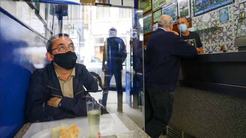 Clientes usam máscara no interior de um café no Porto. Foto: Violeta Santos Moura/Reuters