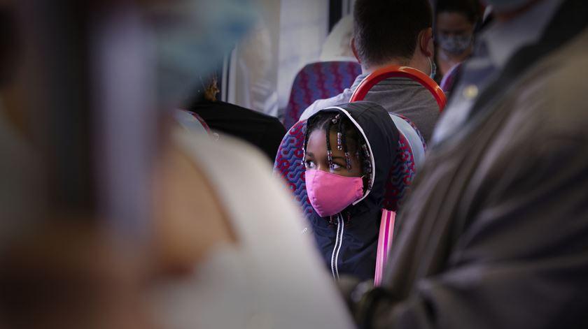 Uma criança viaja, de máscara no rosto, num comboio da CP, na linha de Sintra e Cacém, em Lisboa. Foto: Sofia Freitas Moreira/RR