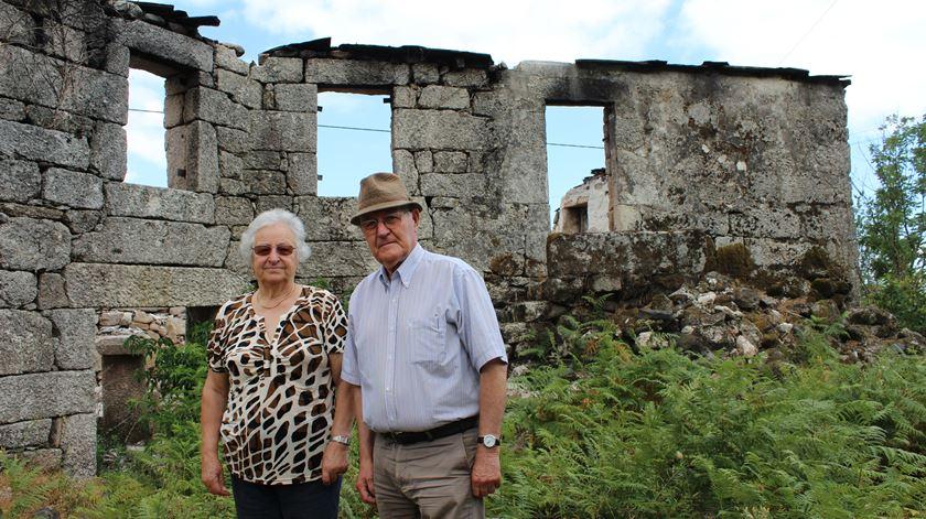 Alda Figueiredo, com o marido, junto à casa ardida do avô. Foto: Liliana Carona/RR