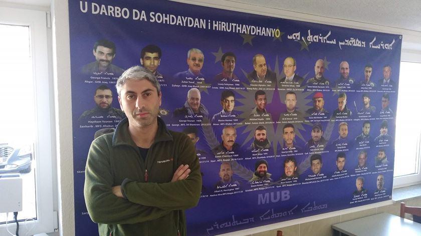 Johan Cosar em frente a um cartaz com as caras e os nomes de membros do Conselho Militar Siríaco mortos em combate. Foto: Filipe d