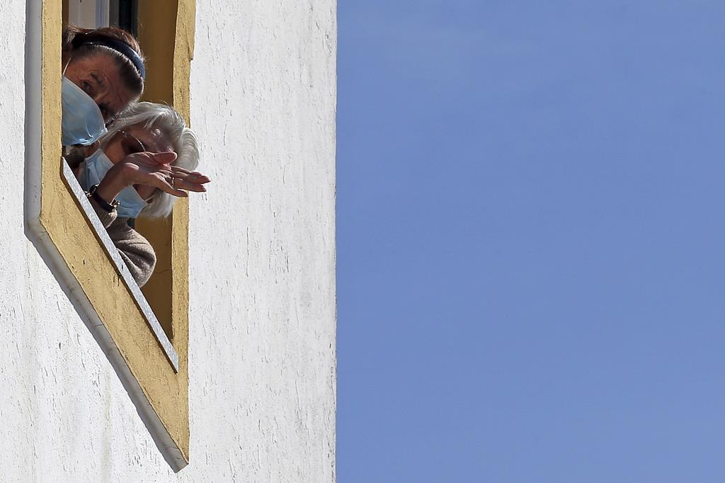 Utentes de um lar em Beja acenam à janela. O concelho vai continuar confinado. Foto: Nuno Veiga/Lusa