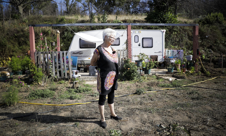 Evelyn vai todos os dias regar as flores que crescem espontaneamente no terreno onde antes estava a sua casa.