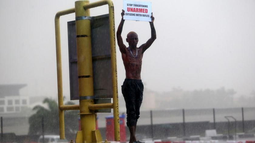 Jovem na Nigéria com cartaz a exigir o fim da violência policial. Foto: Akintunde Akinleye/EPA